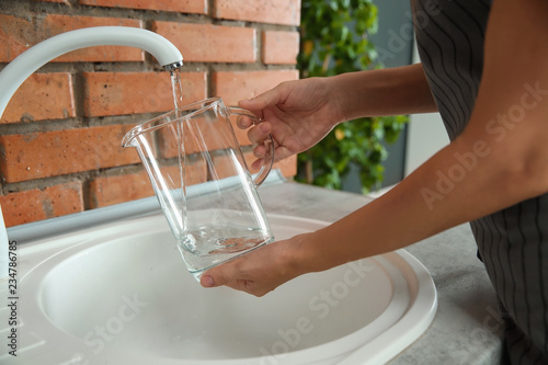Fototapety, obrazy: Woman filling glass pitcher with water, closeup