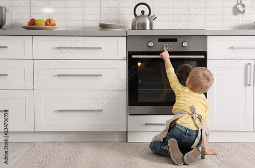 Little boy baking something in oven at home