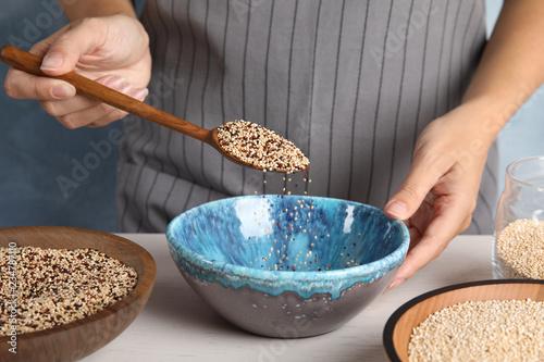 Valokuvatapetti Woman pouring mixed quinoa seeds into bowl at table, closeup