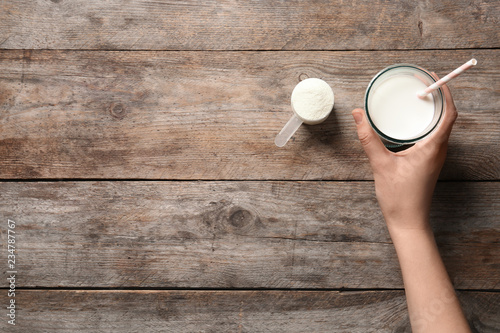 Woman with glass of protein shake at wooden table, top view. Space for text