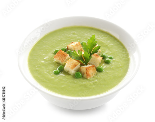 Fresh vegetable detox soup made of green peas with croutons in dish on white background