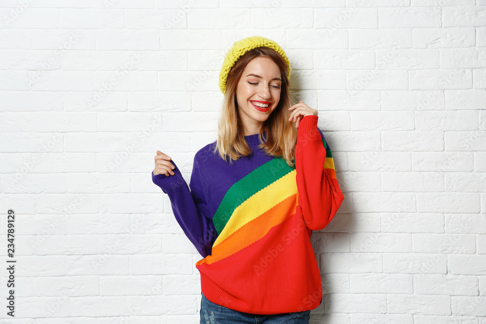 Fototapety, obrazy: Beautiful young woman in warm sweater with hat near white brick wall