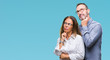 canvas print picture - Middle age hispanic couple in love wearing glasses over isolated background with hand on chin thinking about question, pensive expression. Smiling with thoughtful face. Doubt concept.