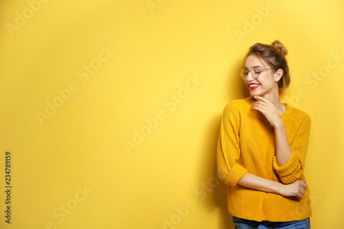 Beautiful young woman in warm sweater on color background. Space for text