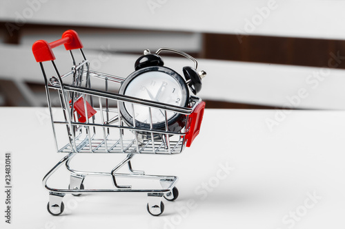 Fotografering  Big alarm clock in shopping cart on a table