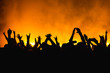 silhouettes of concert crowd in front of bright stage lights. Dancing people with hands on against stage light. Fans burn red flares at rock concert