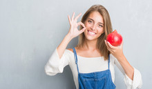 Beautiful Young Woman Over Grunge Grey Wall Holding Pomegranate Doing Ok Sign With Fingers, Excellent Symbol
