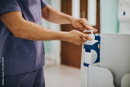 Fotografía  Male nurse disinfecting his hands