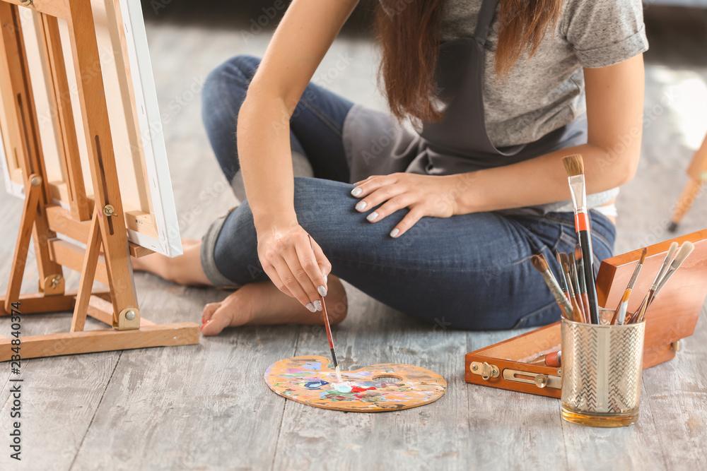 Fototapeta Female artist painting picture in workshop