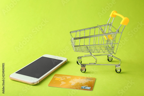 e56199fee94 Small cart with mobile phone and credit card on color background. Online  shopping concept