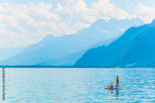 A couple is paddleboarding on geneva lake near Montreaux, Switzerland Fototapeta