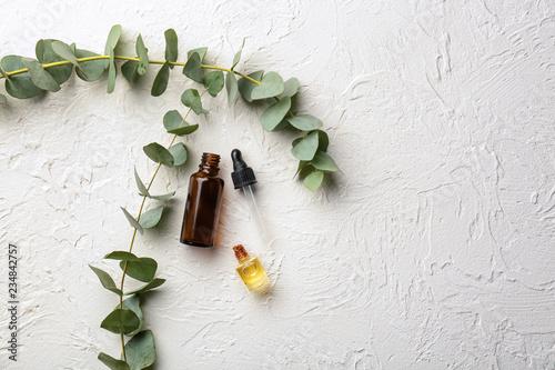 Bottles of eucalyptus essential oil on white background