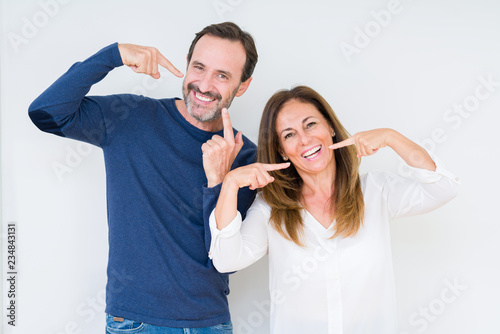 Fotografie, Obraz  Beautiful middle age couple in love over isolated background smiling confident showing and pointing with fingers teeth and mouth