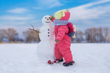 Cute Child Girl Making Snowman At Bright Snowy Place. Winter Outdoor Activities