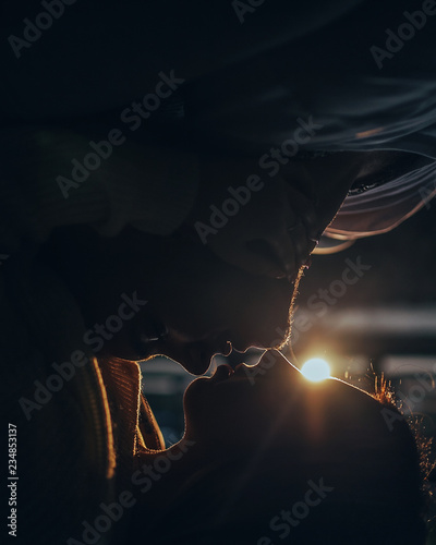 Fotografia  Portrait of the young couple in love lying face to face and kissing against the light of the lamp