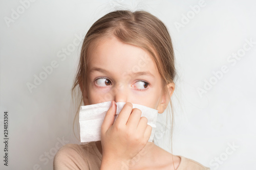 Runny nose in children. A child blows his nose in a handkerchief Tablou Canvas