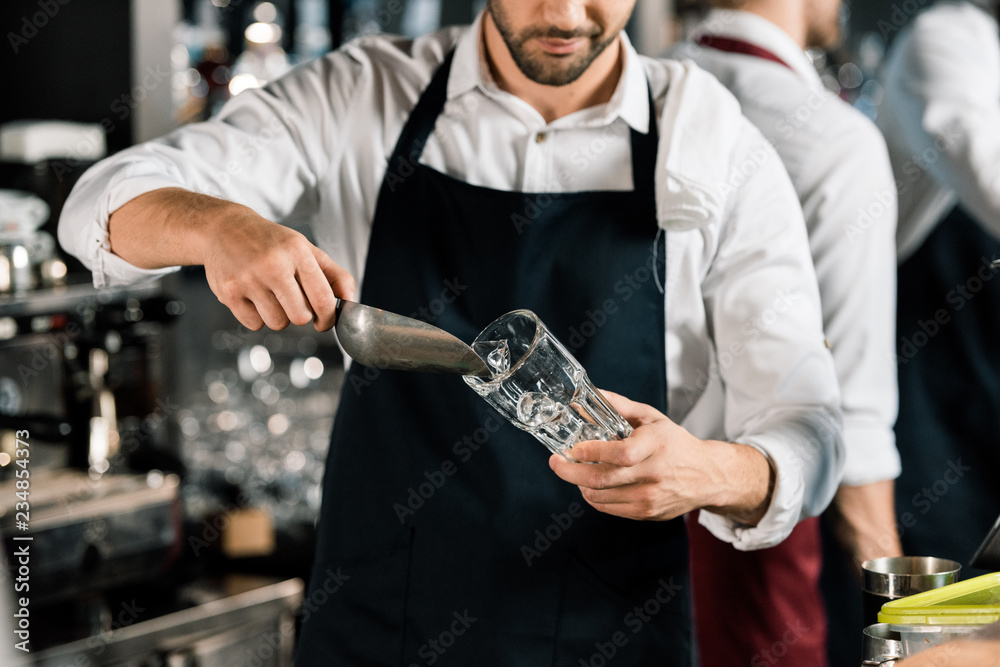 Fototapeta cropped view of  barman in apron putting ice in glass with ice shovel