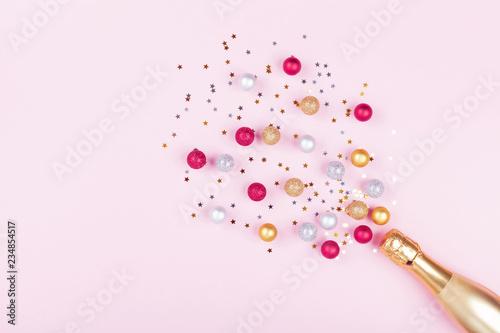 Obraz Champagne bottle with confetti stars and holiday balls on pastel pink background. Christmas pattern. Flat lay style. - fototapety do salonu