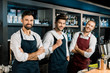 adult barmen team in aprons standing at workplace with arms crossed