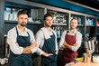 adult barmen team standing at workplace with arms crossed