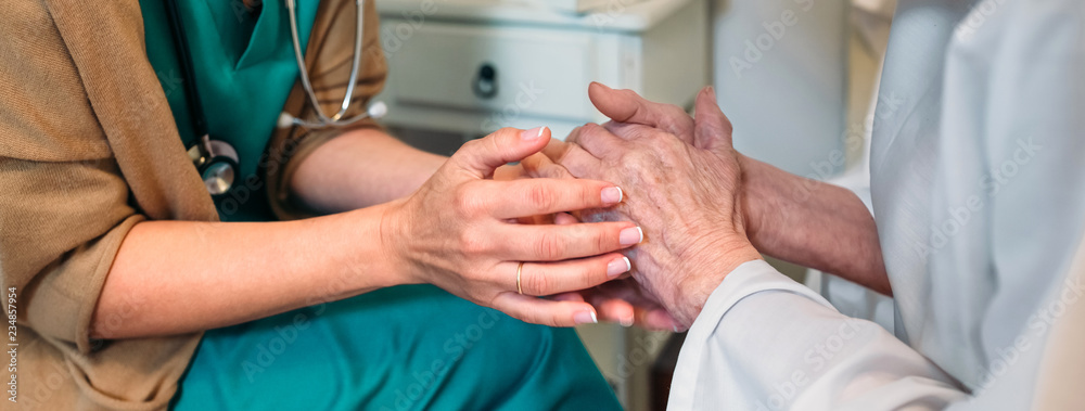 Fototapeta Female doctor giving encouragement to elderly patient by holding her hands