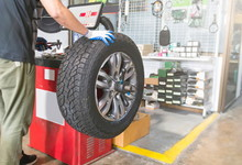 Mechanic Balancing A Car Wheel...