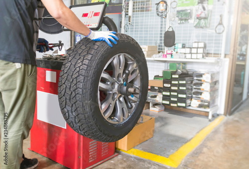Mechanic balancing a car wheel on an automated machine at the garage Canvas Print