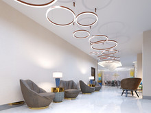 A Modern Reception Area With Large Upholstered Designer Armchairs And A Large Chandelier Of Golden Rings. Side Tables With Lamps And Elegant Vases. White Self-leveling Floor.