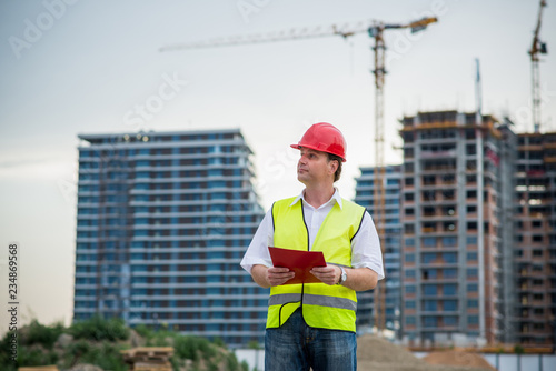 Engineer holding documents on a construction site working on housing project