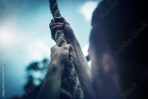 Man climbing a rope during obstacle course