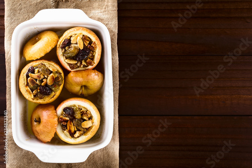 Fresh baked stuffed apple with walnut, almond, raisin, sultana, butter, sugar and cinnamon, a traditional autumn and winter dessert, photographed overhead (Selective Focus on the top of the apples)