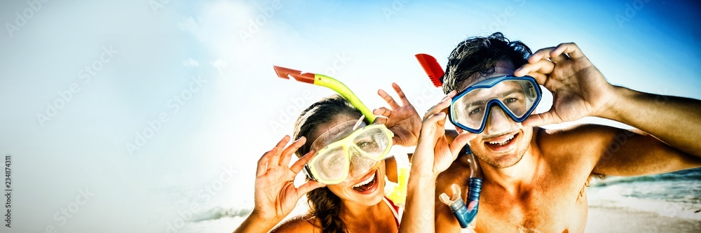 Fototapeta Couple posing with diving mask on beach