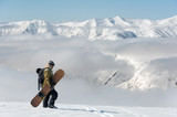 Man walking with the brown snowboard in the mountain resort