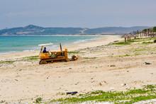 Bulldozer Scavenges On A Sandy Beach In Vietnam