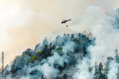 Türaufkleber Hubschrauber helicopter extinguishes forest fire on the slope of fuming mountain