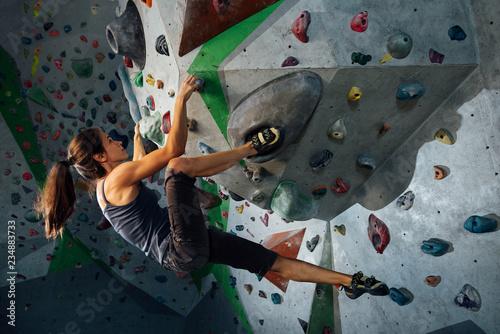 Fototapeta the girl hangs on the ledges climbing the wall in training room obraz