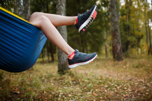 Photo Of Woman With Hanging Legs In Sneakers Lying In Hammock In Woods