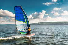 The Man Athlete Rides The Windsurf Over The Waves On Lake