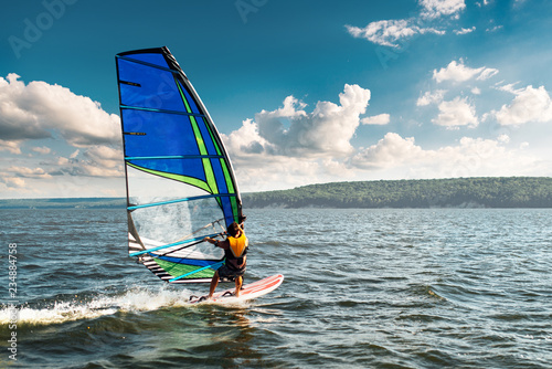 Fotografie, Obraz  the man athlete rides the windsurf over the waves on lake