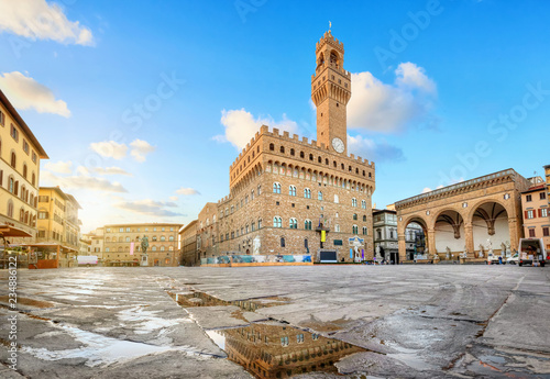Photo Stands Historical buildings Florence, Italy. View of Piazza della Signoria square with Palazzo Vecchio reflecting in a puddle at sunrise