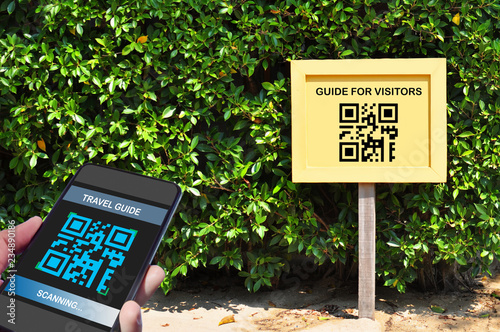 Valokuvatapetti Hand holding smartphone with scanning QR code travel guide screen with guide for