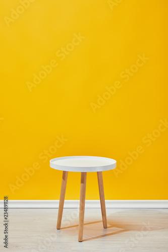 Obraz Minimalistic little wooden table near yellow wall - fototapety do salonu