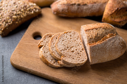 Freshly baked sliced bread on wooden cutting board on the grey stone table, close up.