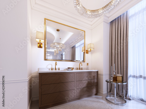 Fotografia Modern wooden vanity with a mirror in a gold frame and sconces on the wall, a low table with decor and a rug with a chandelier