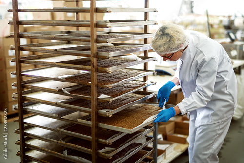 Female worker taking plate with cookies out of shelves. Food factory interior.