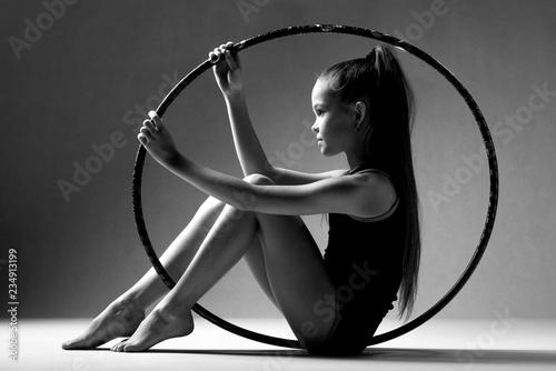 Montage in der Fensternische Gymnastik Portrait of a girl sitting inside a hoop for rhythmic gymnastics. Black background