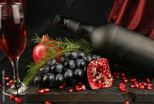 Fotografía  Still-life with pomegranates, fir branches, black grape and bottle on the backgr