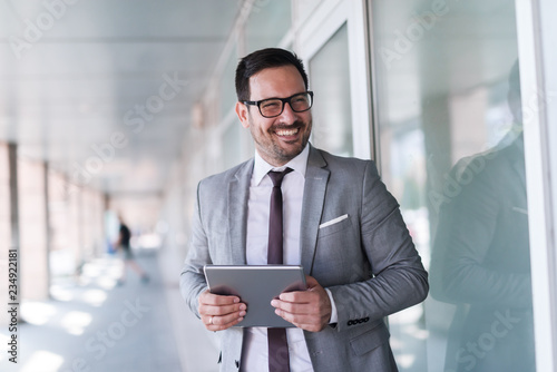 Photo  Close up of smiling businessman dressed in formal wear using tablet while standing near window outdoors