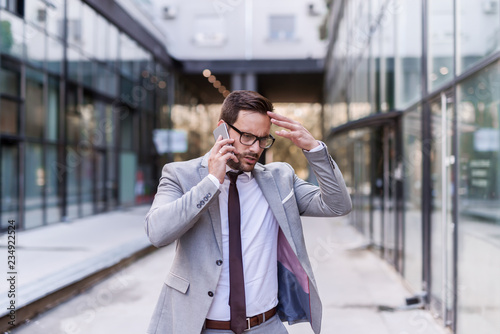 Fotografía  Worried businessman dressed in formal wear using smart phone for a business talk while walking on the street