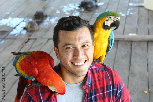 Ethnic man interacting with two gorgeous macaws